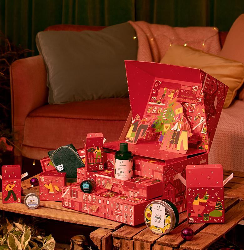 Rød julekalender stående på et bord, med flere lekre produkter. Foto