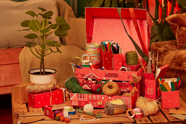 Rød julekalender med sysaker oppi. Foto