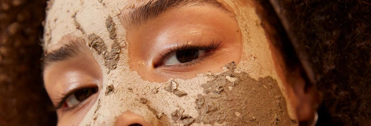 Kvinne med brune øyne og ansiktsmaske i ansiktet. Foto