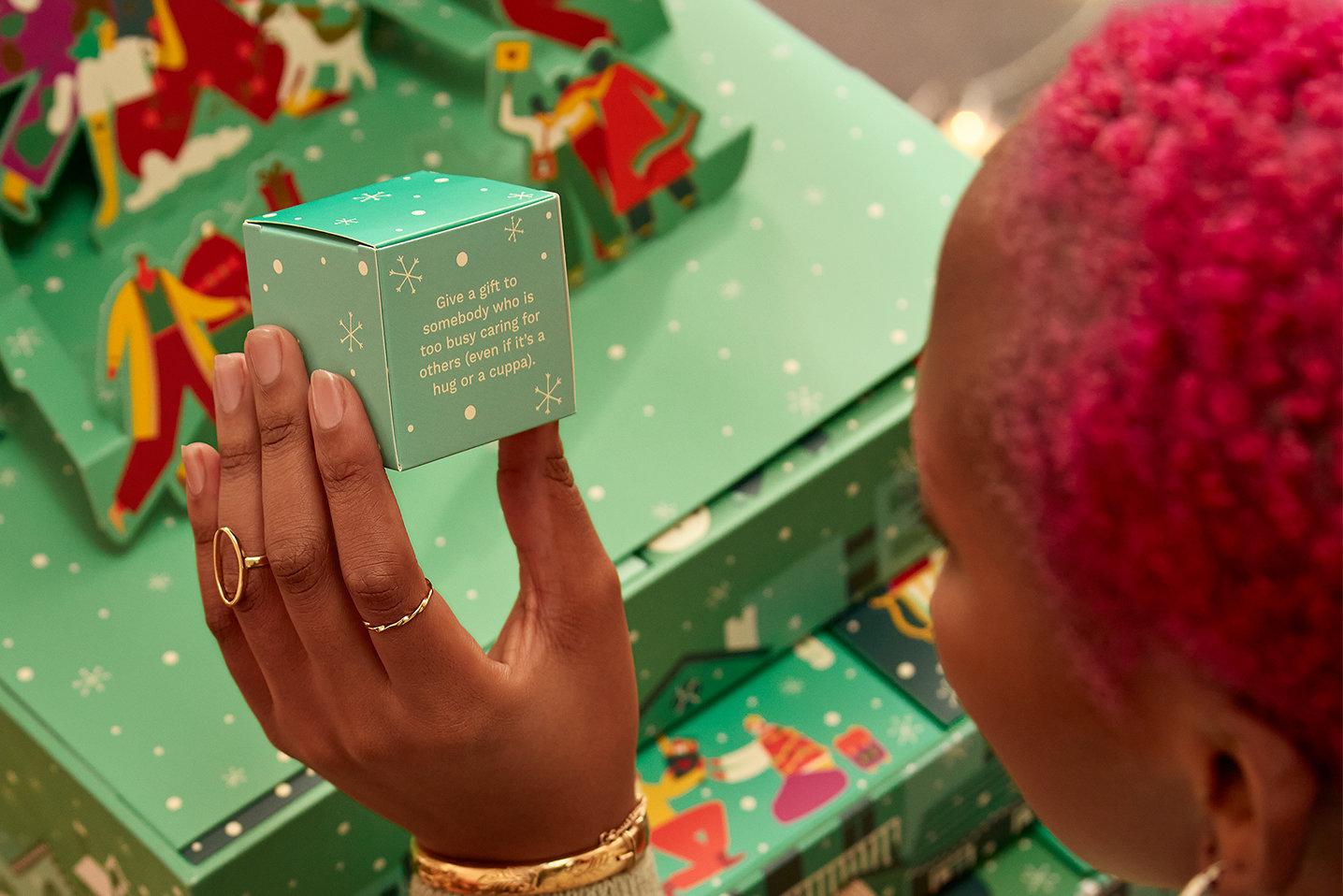 Kvinne med rosa hår holder en grønn eske i hånden med en julekalender i bakgrunnen. Foto