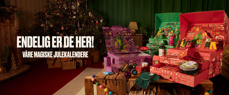 Julekalendere stående på et bord. Mange lekre hudpleieprodukter stående ut av lukene. Foto