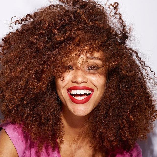 En dame med masse krøller smier bredt. Foto